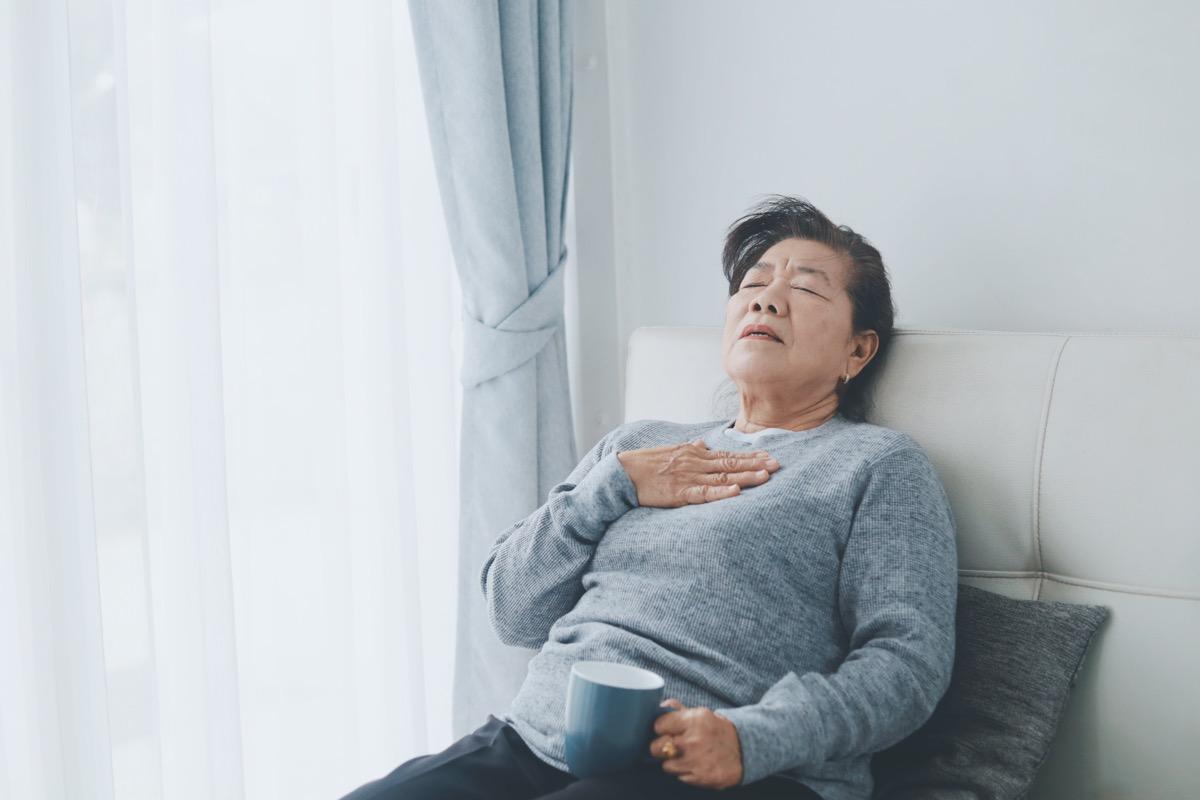 Mulher idosa sentada e com dificuldade para respirar