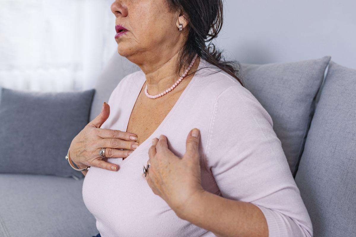 Uma mulher madura, estressada e de meia-idade sente dor e sensibilidade no peito, ela pode ter tido um ataque cardíaco ou derrame.