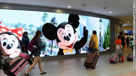 Os viajantes passam por uma placa anunciando o Walt Disney World no Aeroporto Internacional de Orlando no início do fim de semana de 4 de julho, em 2 de julho de 2021.