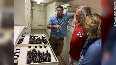 Adam Ferguson (extrema esquerda) e os convidados das coleções do Field Museum são fotografados com espécimes de gambás manchados.