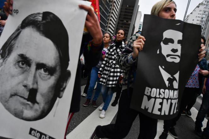 Manifestantes seguram cartazes comparando Jair Bolsonaro a Adolf Hitler em São Paulo, Brasil, em 2018.